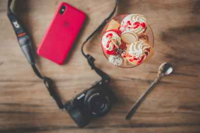 black dslr camera teaspoon ice cream and iphone x
